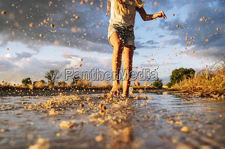 girl splashing water against sky during