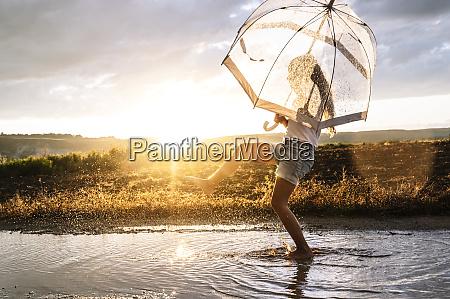 girl with transparent umbrella splashing water