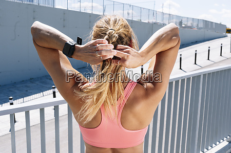 sporty woman braiding blond hair during