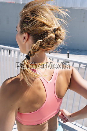 sporty woman with braided hair running