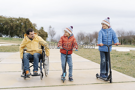 father sitting in wheelchair while boys