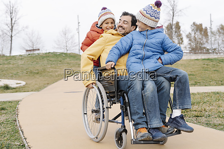 happy man with playful sons riding