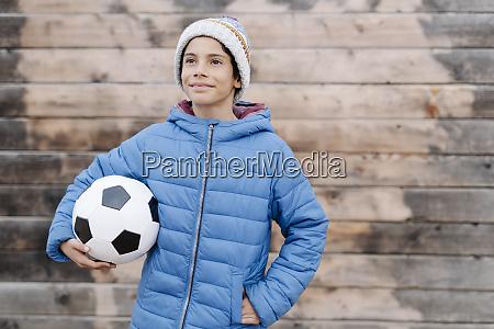 thoughtful boy wearing warm clothing holding