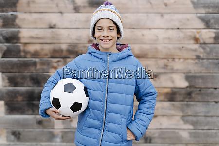 smiling boy wearing warm clothing holding