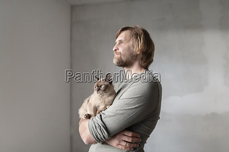 thoughtful man carrying burmese cat during