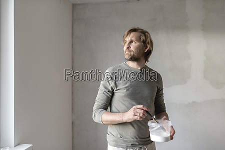 thoughtful man holding paint can at