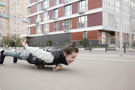 carefree girl lying while skateboarding on