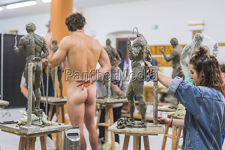 female student forming sculpture nude model