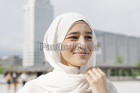 thoughtful teenage girl wearing headscarf in