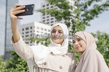 muslim sisters taking selfie through smart