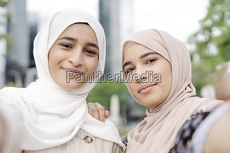 muslim sisters taking selfie in city