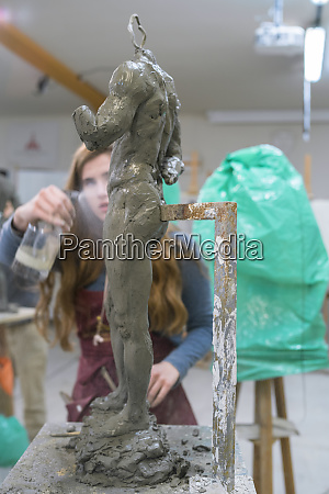female student spraying water on sculpture