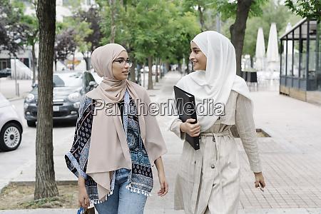 muslim sisters talking while walking on