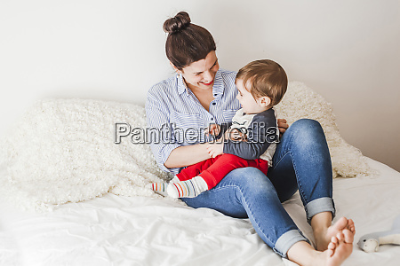 happy mother sitting on bed playing