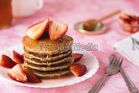 plate of banana pancakes with honey