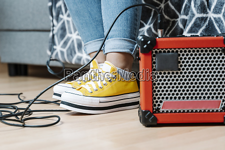 womans legs by amplifier on hardwood