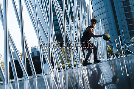 young man playing basketball in modern