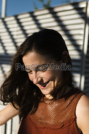 happy woman against shutter during sunny