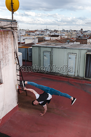 young man breakdancing on building terrace