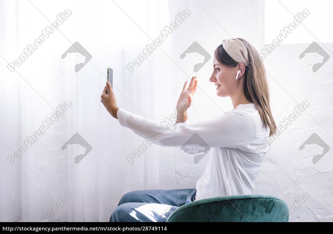 smiling, woman, waving, while, enjoying, video - 28749114
