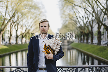 businessman holding model ship at a