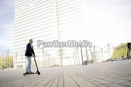 businessman riding kick scooter on city