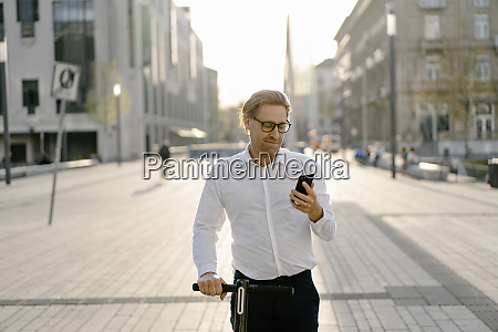 businessman with kick scooter using smartphone