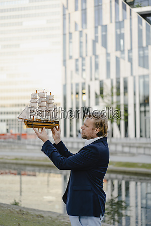 businessman holding model ship in the
