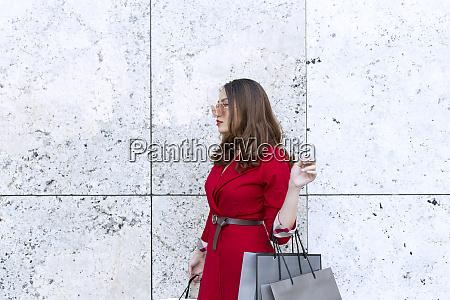 young woman wearing sunglasses carrying shopping