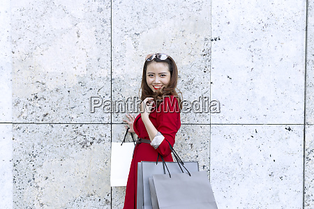 smiling woman carrying shopping bags while