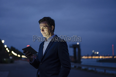 mature businessman using tablet at the