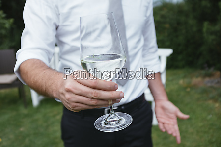 mid section of man holding glass