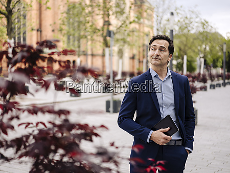 mature businessman holding tablet in the