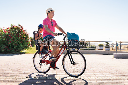 happy father and daughter riding bicycle