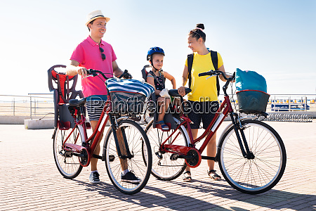 family riding bicycle outside