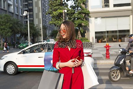 cheerful woman carrying shopping bags walking