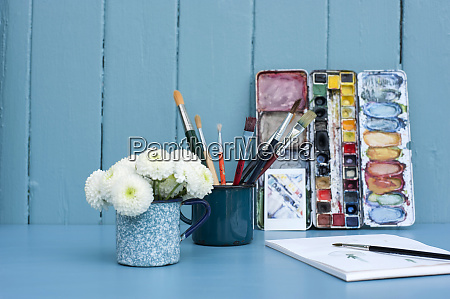 mugs with paintbrushes and blooming bellis