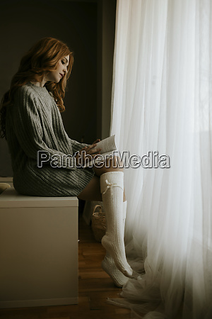 blond woman at home reading a