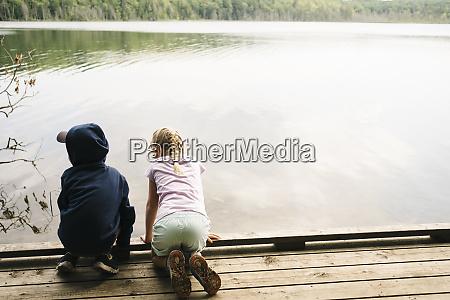 siblings on pier over lake