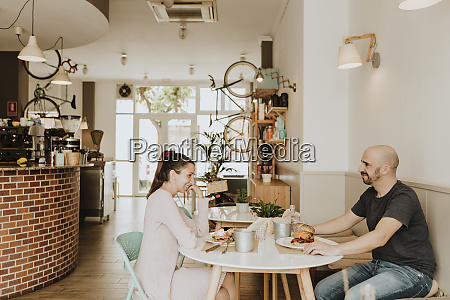 smiling man and woman sitting at