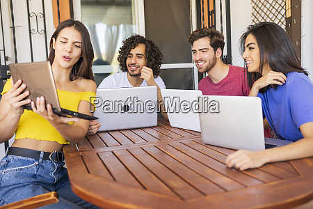 young woman showing laptop to smiling