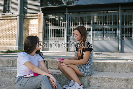 smiling young female friends talking while