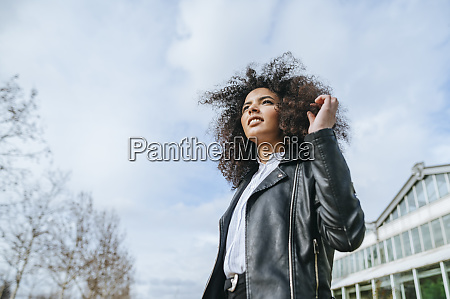 afro woman looking away against sky