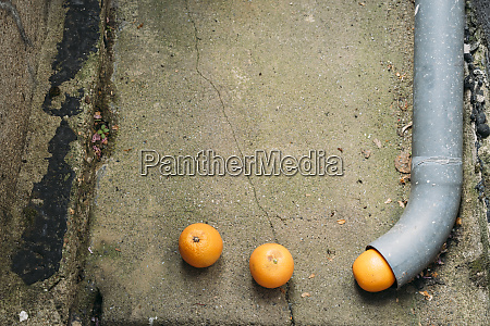 three oranges disappearing in pipe