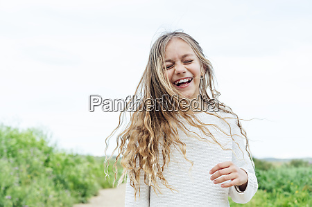carefree blond girl standing with eyes