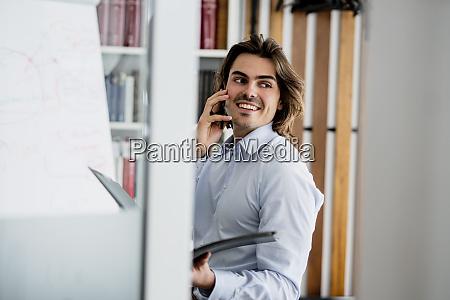 smiling businessman talking over smart phone
