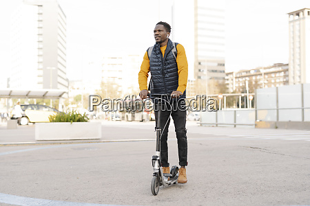 young man riding e scooter in