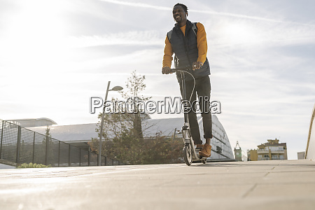 happy young man riding e scooter