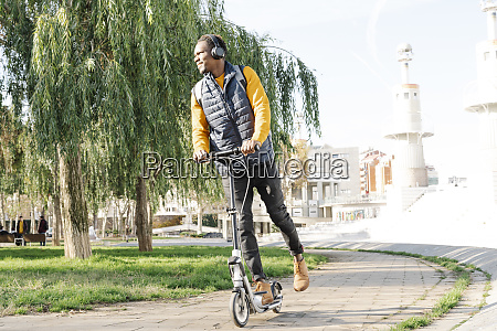 young man with headphones riding e