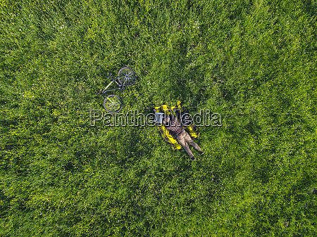 man lying on grass and using